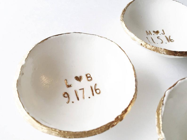 White ring dish with gold rim and gold engravings of initials and date