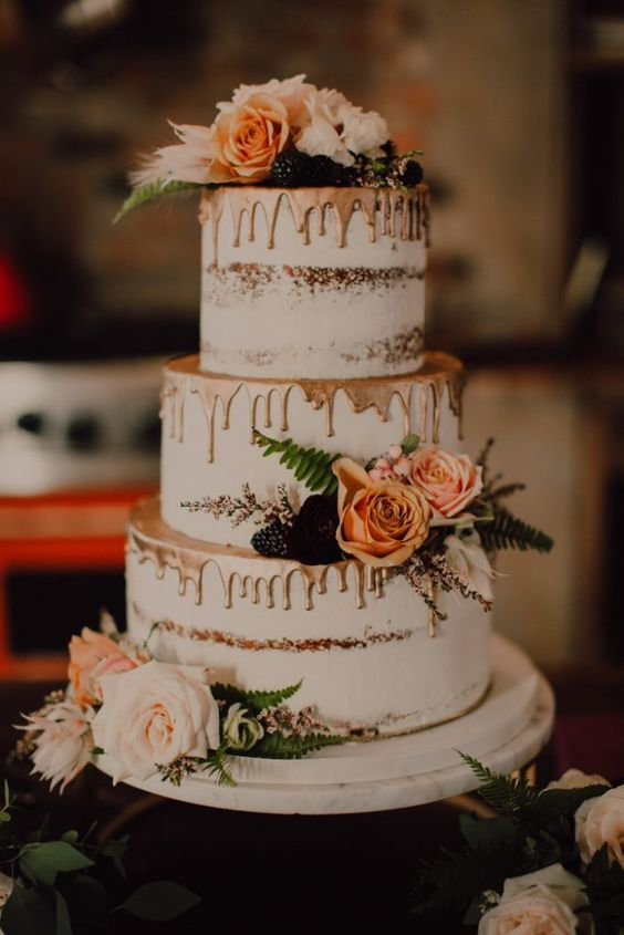 naked cake with roses, greenery, and metallic designs