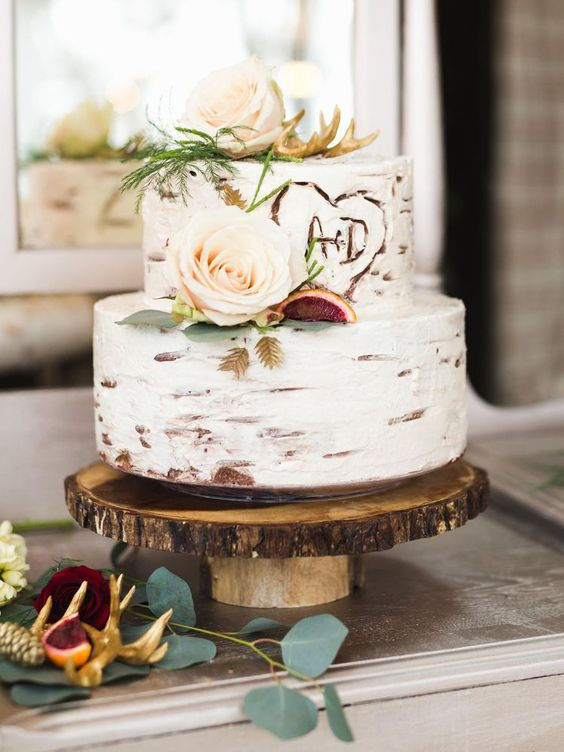 rustic wedding cake frosted to look like dogwood on wood cake stand