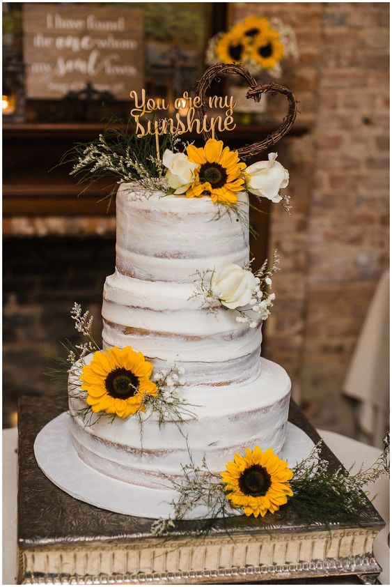 simple rustic wedding cake with flowers and wooden heart cake topper