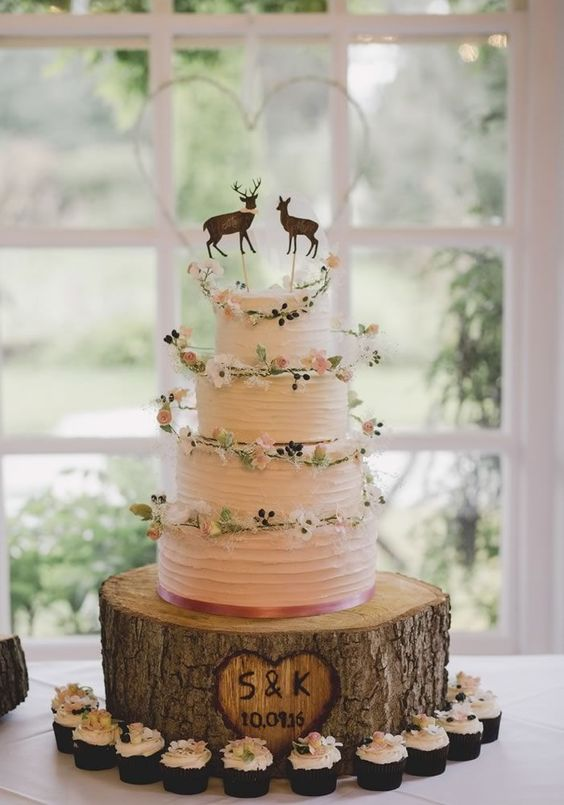 4-tiered cake with flower rings on each layer and deer cake toppers