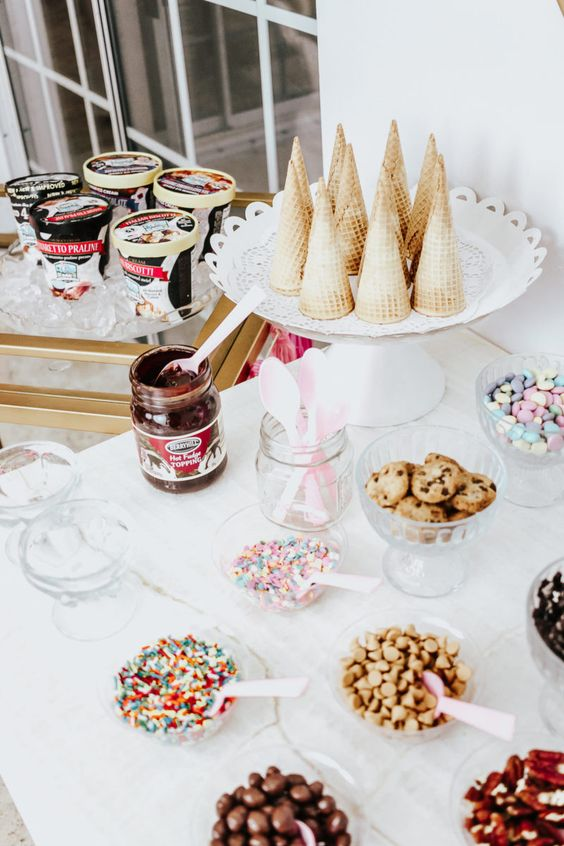 ice cream bar with cones, toppings, and sauce