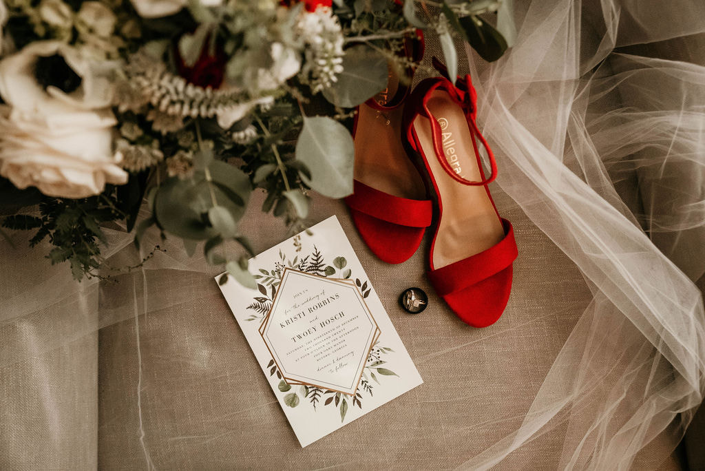 Wedding invitation with red bridal shoes, and a bridal bouquet of flowers.