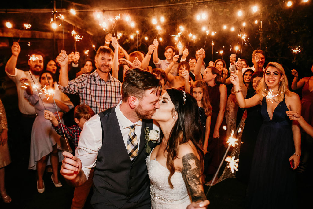 Bride and groom kissing while they and guests hold sparklers under reception lights