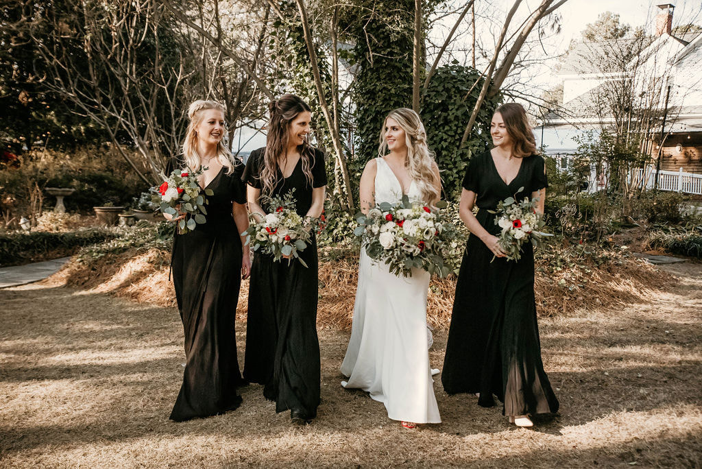 Bride with her bridesmaids wearing black bridesmaids dresses at an outdoor garden venue.