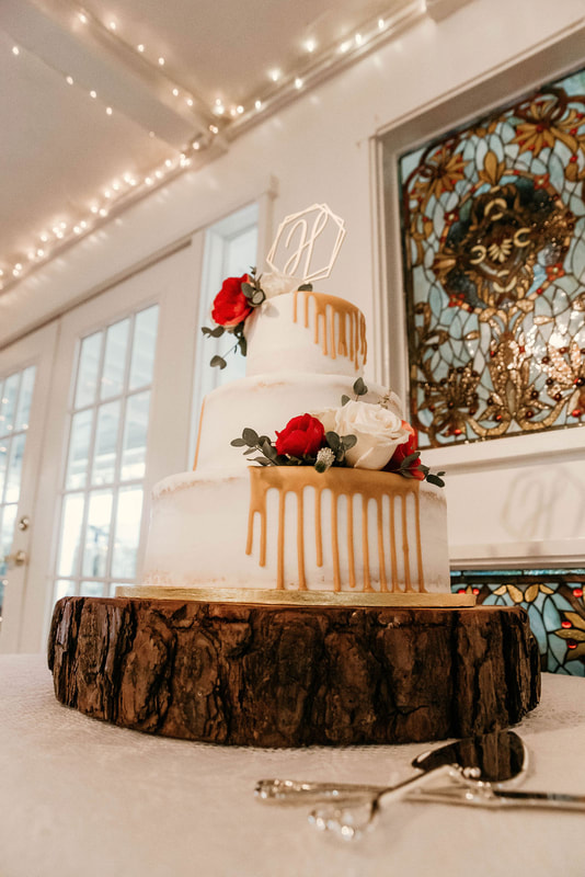 Winter white wedding cake with red and white roses and a caramel dripped icing on a wood slice.