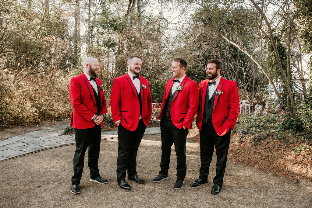 Groom and his groomsmen wearing red Christmas suits for December outdoor wedding.