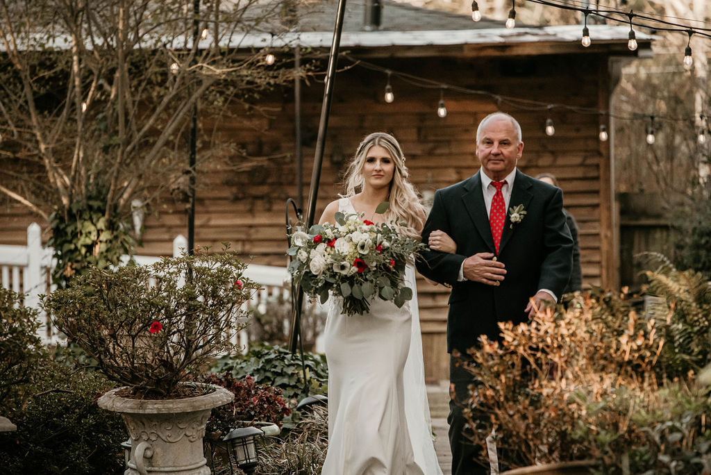 Dad walking bride down the aisle for outdoor wedding ceremony in December.
