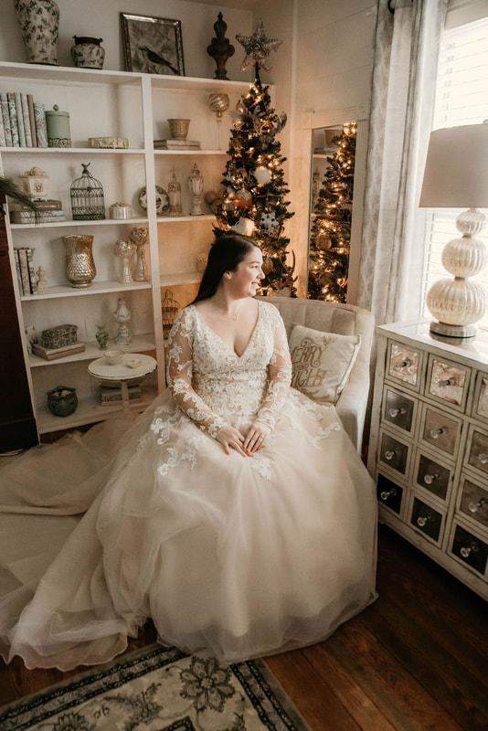 bride with long-sleeved lace dress sitting in farmhouse room decorated for Christmas