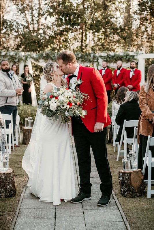 Bride and groom kissing at their outdoor wedding ceremony in December.