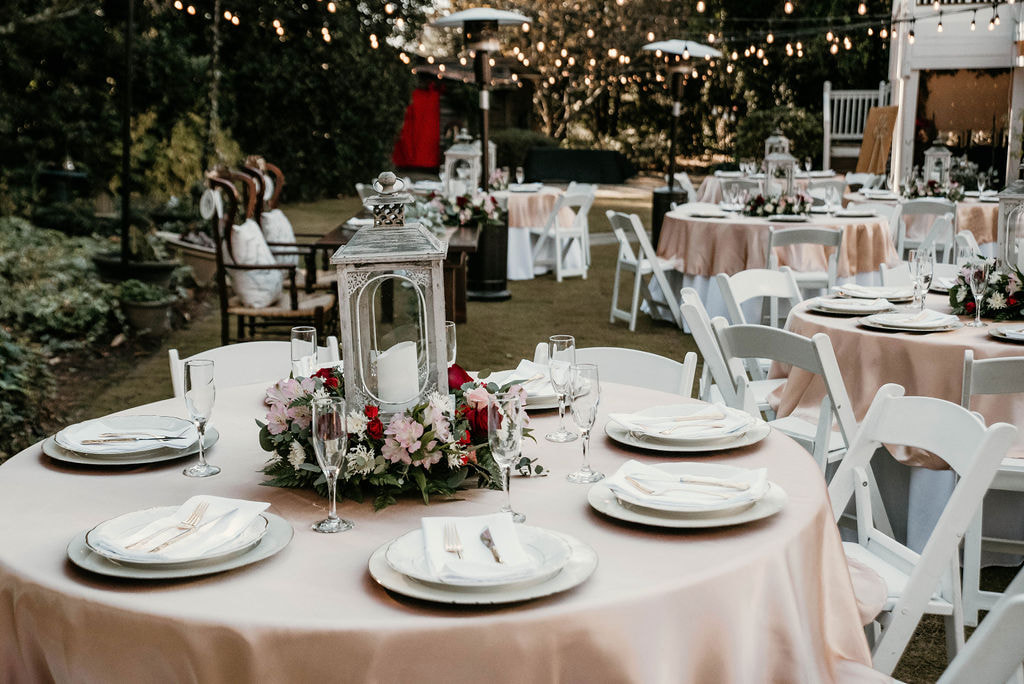 reception tables with champagne overlays and floral and lantern centerpieces