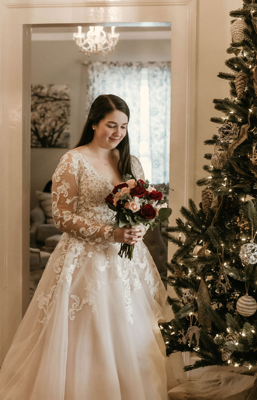 winter bride by Christmas tree holding red and blush bouquet