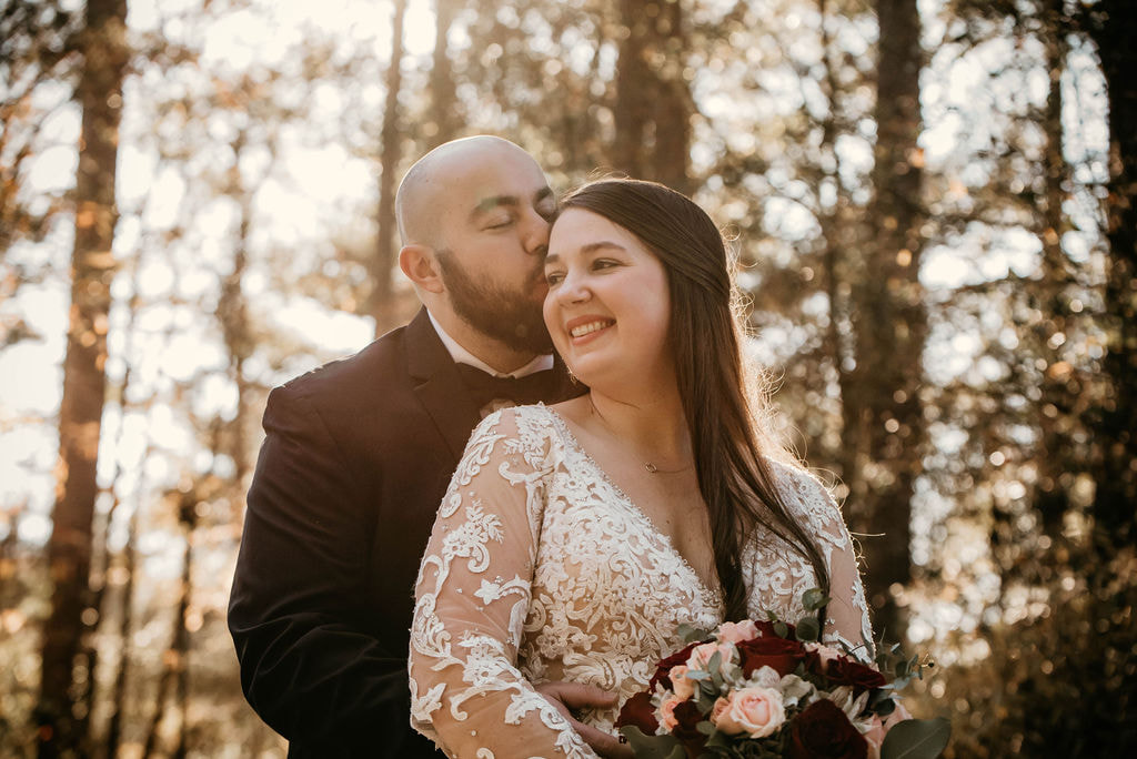 groom kisses bride's head surrounded by trees at Four Oaks Manor venue