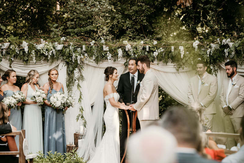 couple at altar decorated with theatre fabric and greenery