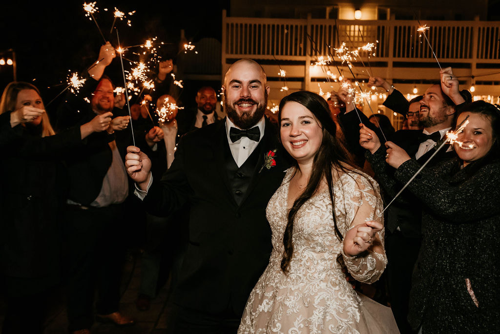 couple holding sparklers with guests for mock grand exit at winter reception