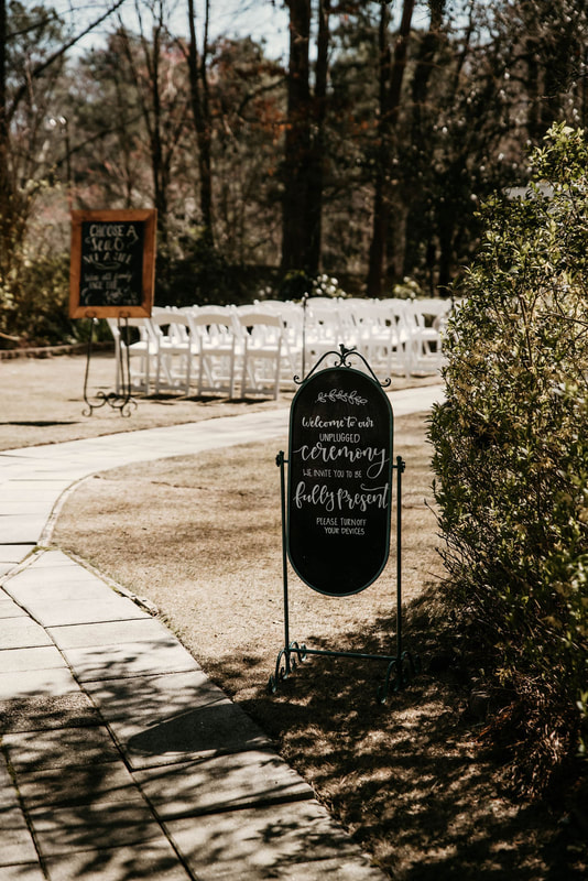 unplugged ceremony chalkboard sign along path to outdoor ceremony area