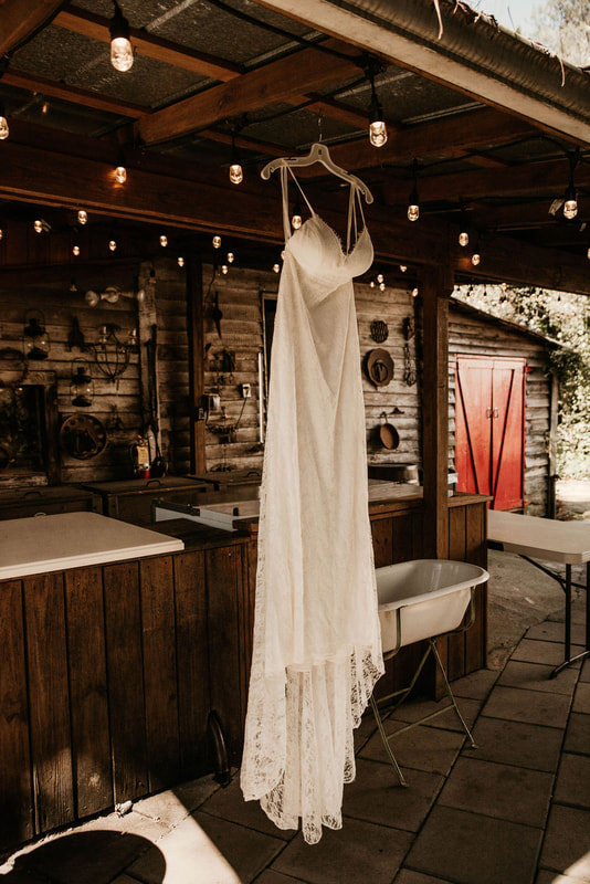 simple lace wedding dress hanging from roof of smoke house