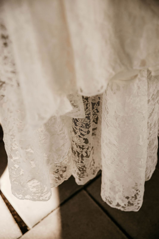closeup shot of lace wedding dress with floral laced train
