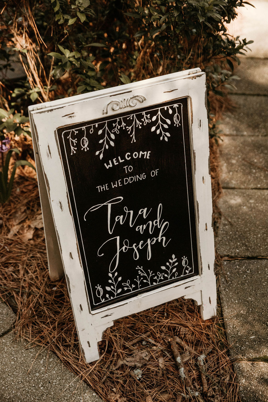 white chalkboard welcome sign with flower and leaf designs