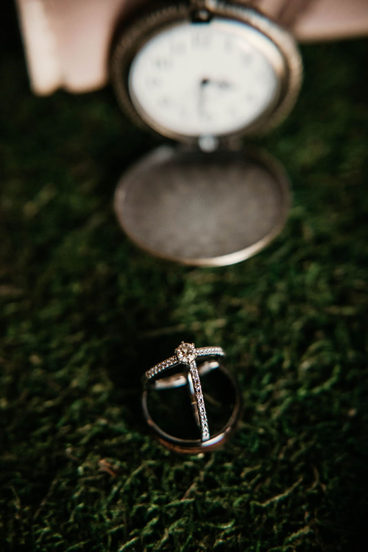 detail photo with couple's rings on turf with vintage pocket watch