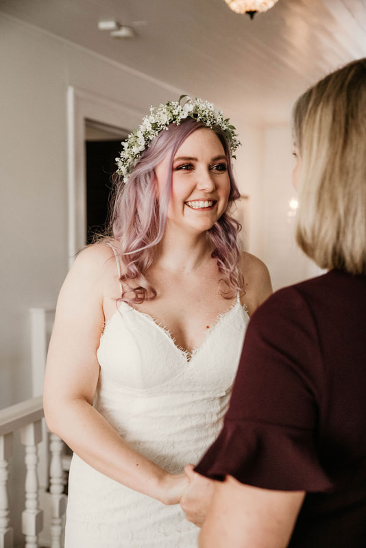 bride with lace dress and flower crown smiling at mom while getting ready
