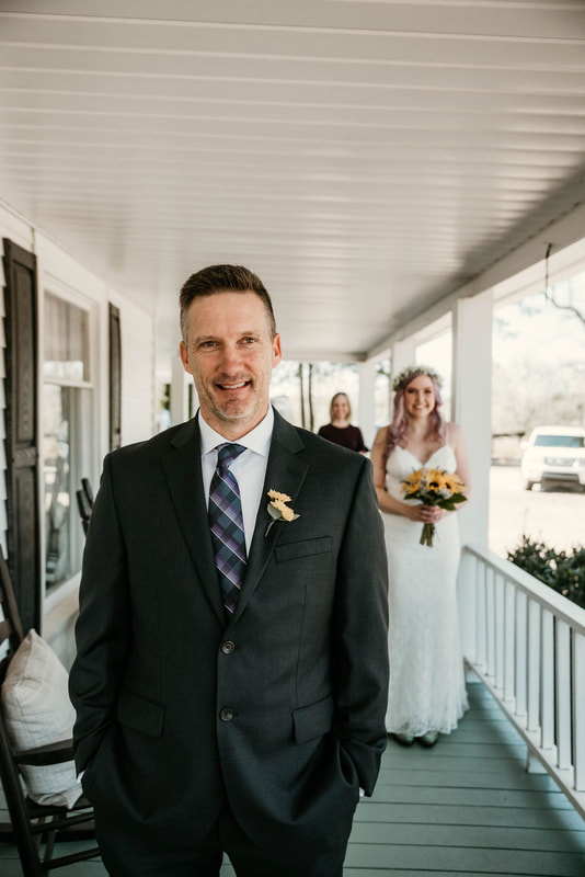 bride poses behind father on farmhouse front porch for first look