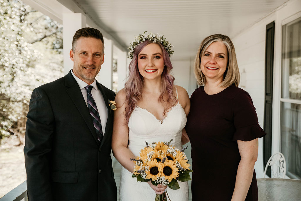 bride holding sunflower bouquet posing with parents