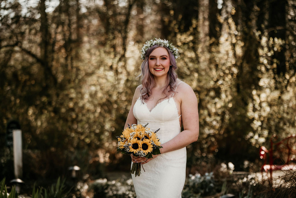 bride with sunflower bouquet posing in forest during March wedding