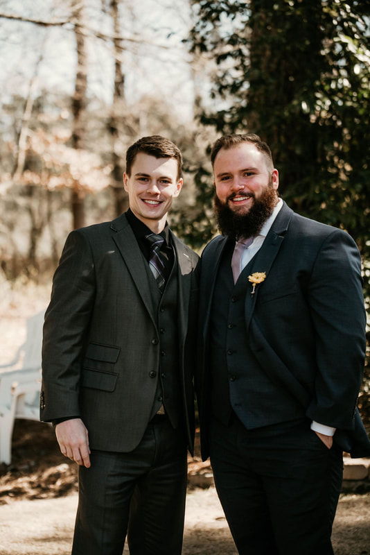 groom posing with friend near outdoor ceremony area