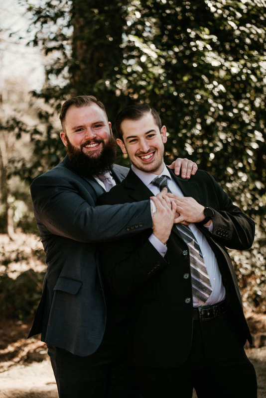 groom laughing and posing with friend with hug from behind