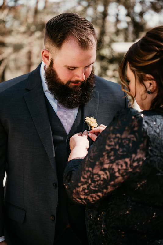 mother of the groom pinning yellow boutonniere on son's suit jacket