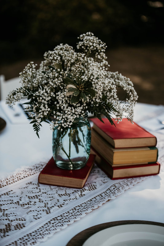 centerpiece with vintage books and baby's breath arrangement on lace and burlap runners