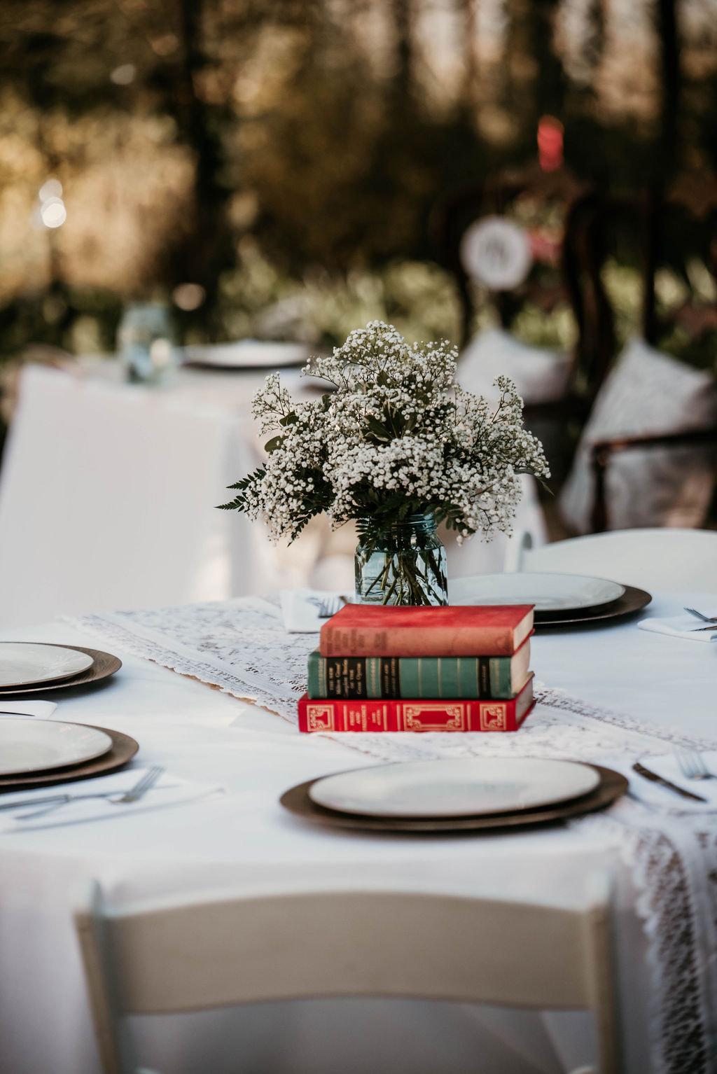 table decor with vintage books, flower arrangements, wood chargers with china