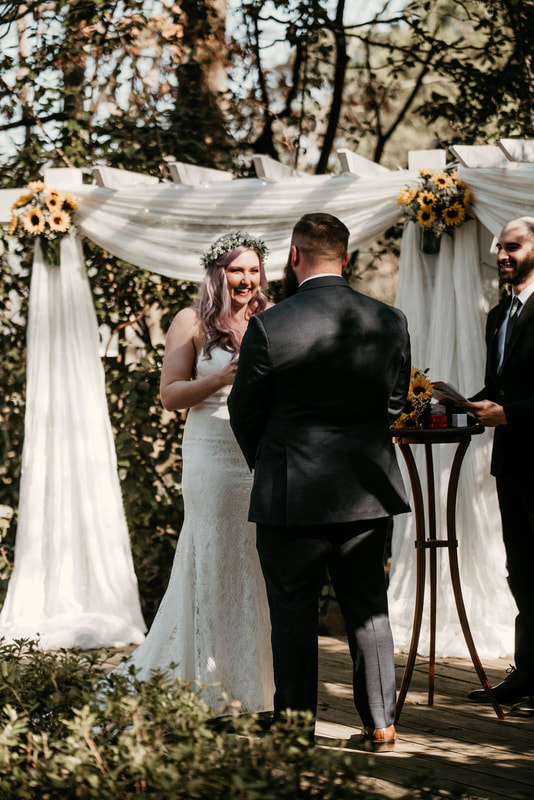 bride saying vows during March ceremony at altar decorated with white chiffon and sunflowers