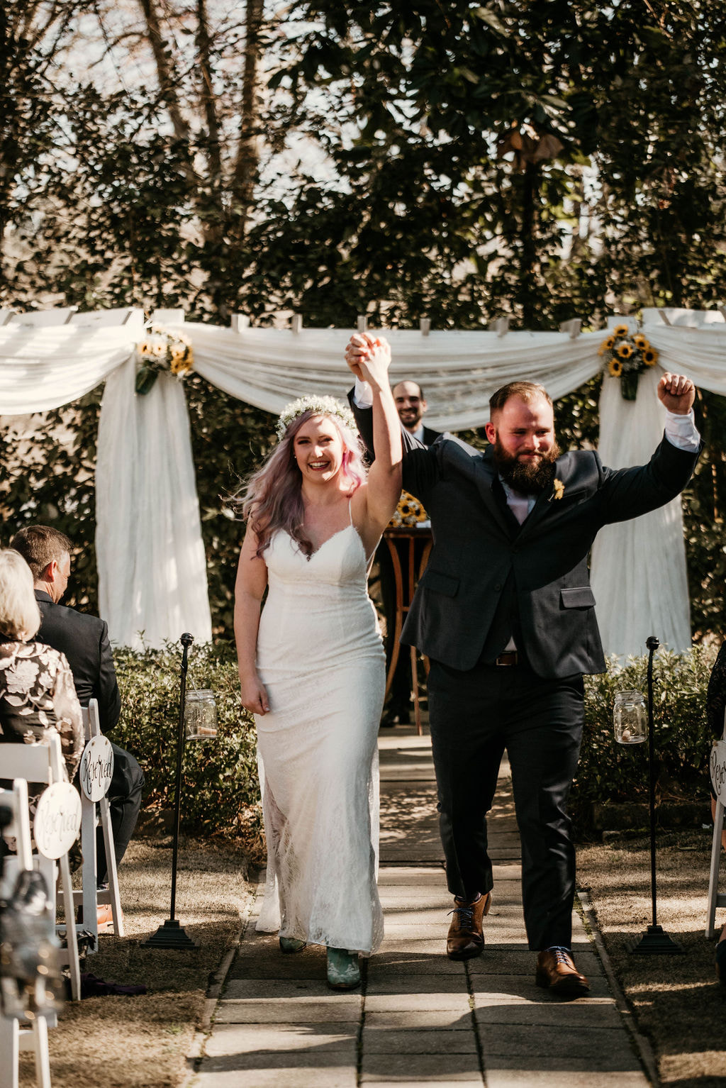 couple holds hands up in celebration together after wedding ceremony