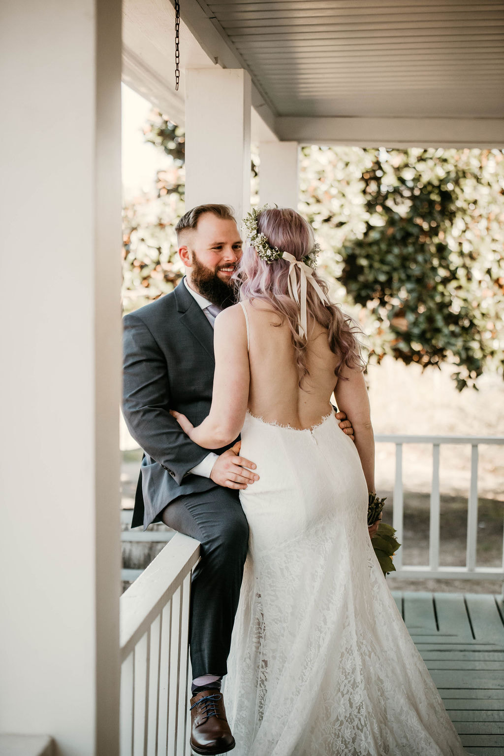 groom sitting on farmhouse porch railing and hugging bride
