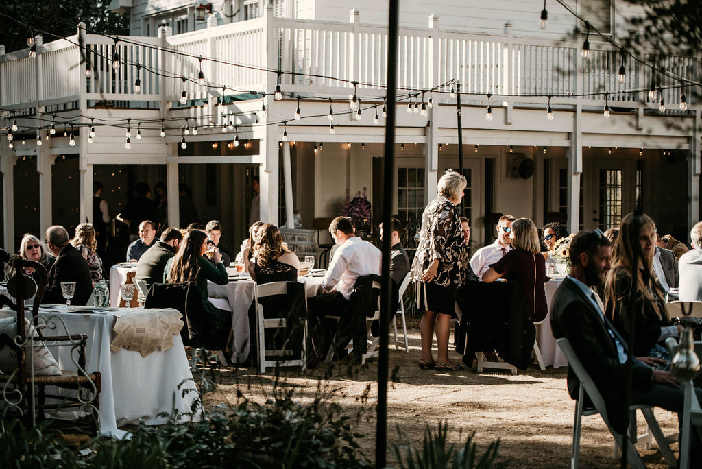 wedding guests at outdoor reception under hanging lights
