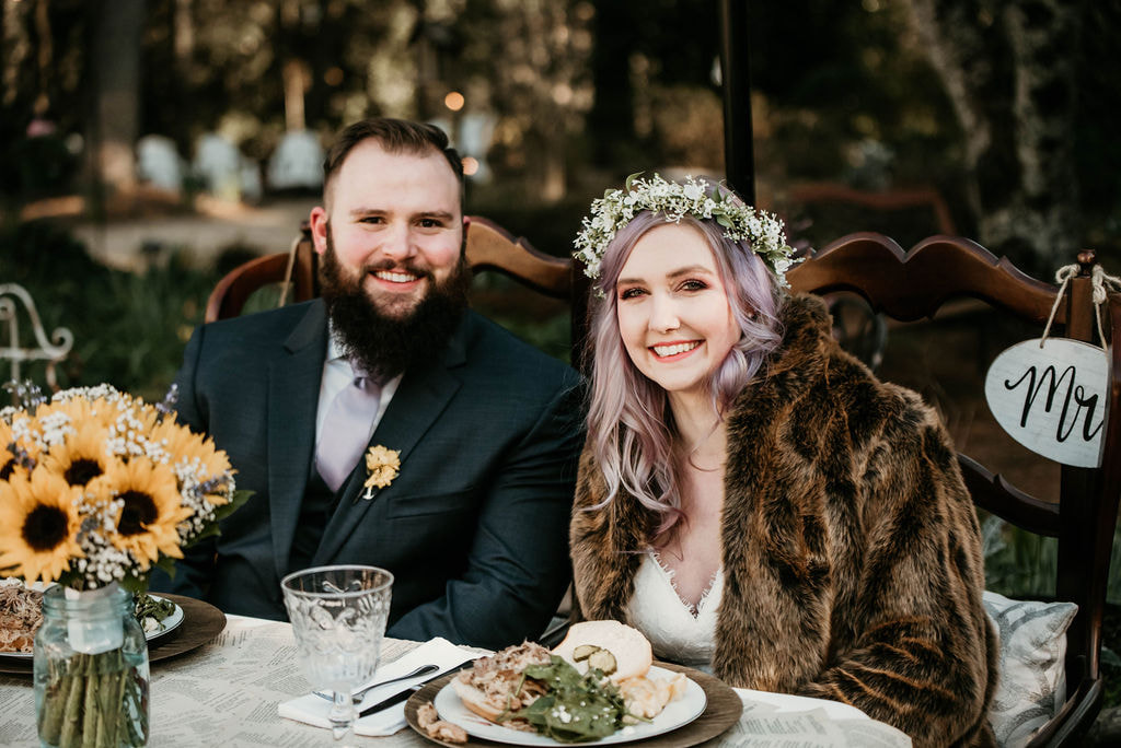 bride wearing faux fur jacket and sitting with groom at reception sweetheart table