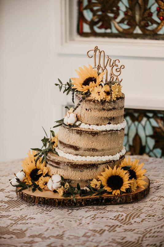 rustic naked cake with sunflowers, gold cake topper, and cotton