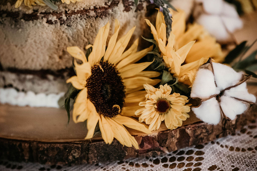 sunflowers and cotton decorations on rustic cake