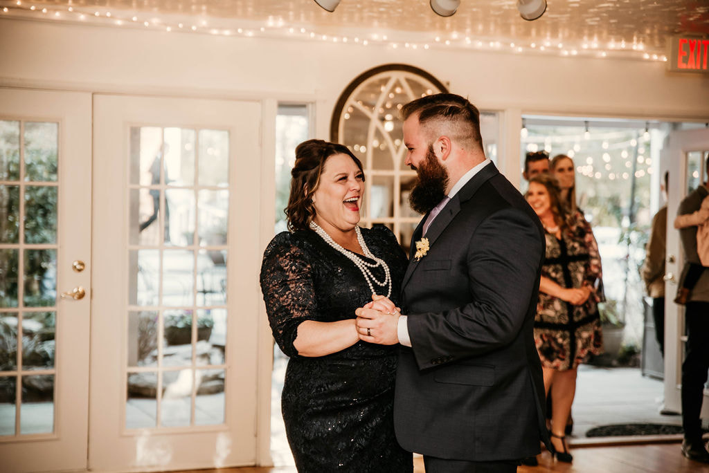 groom dances and laughs with mother in Four Oaks Manor's carriage house