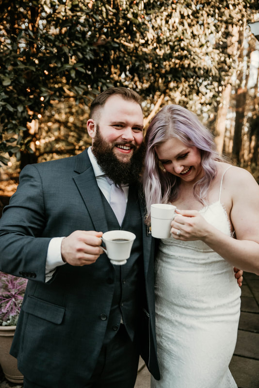 bride with lavender-colored hair laughing with groom while both holding china cups with coffee