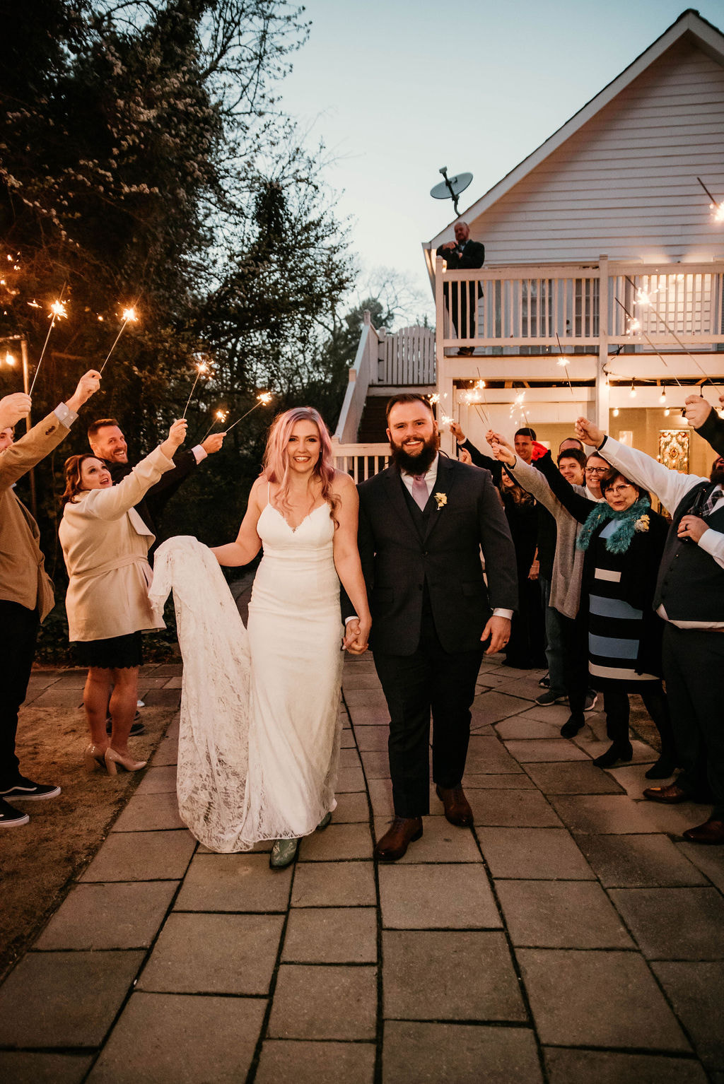 Tara and Joseph smiling while guests hold sparklers