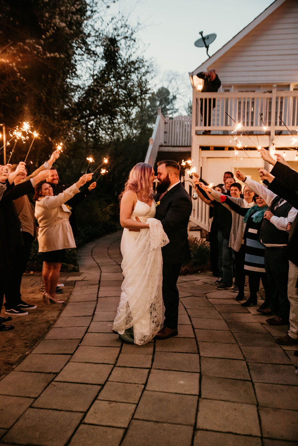Couple smiling while guests look on during sparkler grand exit