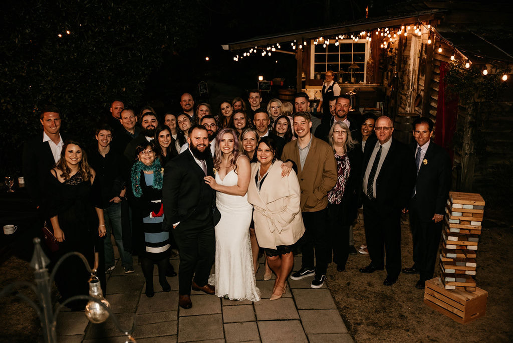 Tara and Joseph pose with all their wedding guests at night