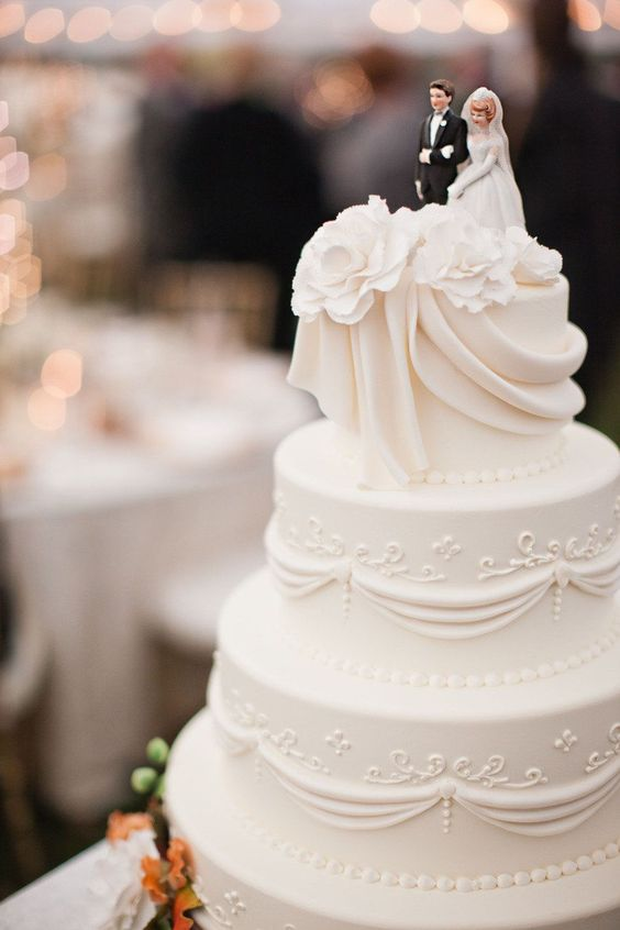 traditional white wedding cake with fondant and classic piping